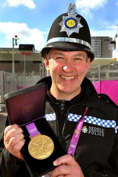 British policeman Mark Riddick holds an Olympic Gold Medal during the Village Mayors trip around the London 2012 Olympic Athletes village in east London, on August 2, 2012.
