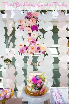 A first birthday garden party dessert table with shades of pink and purple and lots of sweet treats!