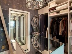 "As seen on HGTV's ""Genevieve's Renovation,"" the dressing area in Genevieve Gorder's master suite is spacious, with an elegant chandelier as well as a stackable washer and dryer. A mirrored island countertop reflects the light from the sparkling chandelier, brightening the room's dark purple wallpaper. The glass shower entry is a convenient addition to the closet."
