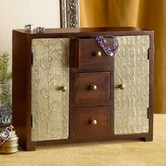 STAMPED TIN JEWELRY BOX - Open the stamped metal doors of this tin jewelry box to reveal rotating dowels with hooks for necklaces and bracelets...three drawers stow rings and earrings.