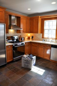 Kitchen | Oak Cabinet | White Subway Tile backsplash | Dark Natural Stone Tile Floor