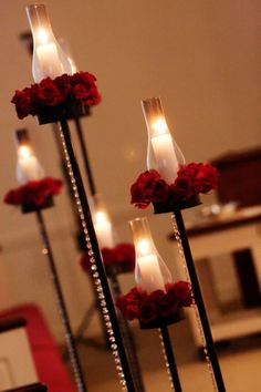 I like the classic simplicity of these hurricane candles surrounded by a ring of red roses - imagine them lining your aisle or a version of them used as centerpieces
