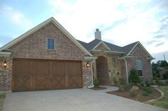 Front elevation, full stone and brick home, cedar garage doors #mcbeehomes
