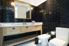 Galli chose the guest bath's high-gloss black subway tiles as a nod to New York City, one of her go-to travel destinations. An oak custom vanity topped with Carrara marble and a matching mirror add warmth | archdigest.com
