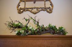 Driftwood, intricately adorned with flowers, plants, and pods