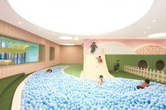 Karv One Design builds school around giant slide and ball pit.