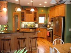 Honey Oak Kitchen Cabinets with Black Countertops and green walls | Best Paint Colors For Kitchens With Oak Cabinets