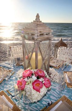 We love this rustic beach reception set-up with a lantern and classic bouquet as the centerpiece | Kelly McWilliams of Weddings by Socialites