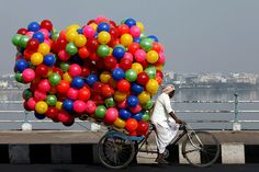 """A rickshaw puller carried plastic balls for sale in the southern Indian city of Hyderabad, Andhra Pradesh"" #India"