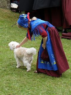 A little girl in Faroese National Costume playing with a dog at the Day of Ólavsøka 2009, via Flickr.
