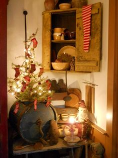 Primitive Christmas Tree & Rustic Needfuls...old churn stuffed with a handmade red stockings adorned lighted tree & prim mustard cupboard.  Love the gingerbread men peeking onto this early and country style Christmas display.