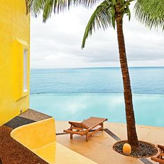 Tropical hues of blue, yellow, and pink dot the rugged waterfront terrain at Costa Careyes resort. The kaleidoscope of cliffside villas, casitas, and even castles stands high above the water, artfully arranged on seven miles of shoreline.