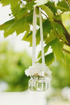 Bouquet of hanging flowers with ribbon. This would be awesome in a backyard wedding!