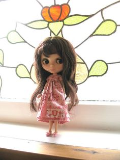 My lovely 1972 Kenner Blythe doll medium brunette standing in front of my gorgeous 80+ year old stained glass rose window.  You can still get vintage Blythe dolls online and my website has organized Ebay auctions to help you find the best deals and best sellers too http://bigeyedbuys.com