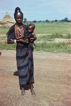Fulbe woman with child ca. 1975 near Burkina Faso Border/Niger/West Afica. University of Wisconsin--Madison Maria Theresa, African Textiles, Thinking Day, Mother And Father, Babywearing, Fathers, Nursing, Nice Dresses, Globe