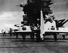 Flight deck crew pushing a SBD-2 Dauntless aircraft into position aboard USS Lexington, 1941