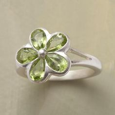 Peridot Daisy love.@Liz Casey, did you see this? replace 2-3 of the peridots with amethyst and it's our ring!(ish)
