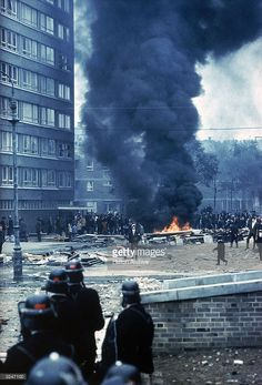 Police in riot gear watch from a distance as crowds of people stand around a large fire in the rubble during the Ulster riots in Londonderry. Northern Ireland Troubles, Irish Republican Army, Apocalypse Art, Protest Art, World 2020, Londonderry, Irish Celtic, Explosions, Photo Journal