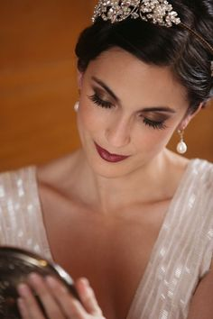 Beautiful makeup for a fall or winter wedding: Deep maroon lips, lush eyelashes, and bronzed brown shadow.