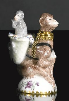 A Chelsea gilt-metal mounted scent bottle and stopper in the form of a monkey and its young, circa 1755 modelled sat on its haunches wearing a basket on its back filled with flowers from which rises its young, it's chained detachable head forming the stopper upon a small mound base painted with flower sprigs and larger spray to the underside, with gilt-dentil border modeller Charles Gouyne  ?  co  founder of Chelsea with Nicholas Sprimont both were  Huguenot Refugees