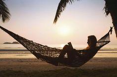 woman reading book beach sunset hammock palm trees
