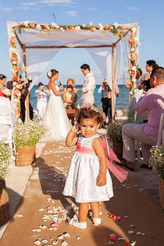 """A flower girl secures the best possible vantage point for the """"I dos."""""""
