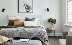The norsuHOME - Main Bedroom  Photographer: Lisa Cohen Stylist: Beck Simon  Paint: Dulux Terrace White Carpet: Godfrey Hirst  Shutters: Carpet Court  Products:  Rubn Wall lights, Lola Donoghue Zebra Girl print, The Cullin Design Bedhead and Bench seat, norsu cushions, Honey Honey Creations knitted throw, GlobeWest Felix Chair & Henley Side Table (all available at www.norsu.com.au)
