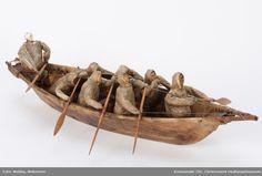 Modell av en Umiaq konebåt. Modell med 7 roere og en mann ved styreåren. Teknikk: Båtens skjelett og årer av tre. Båten trukket med selskinn. Anorakkene av tarmskinn. Kvinnehodene av tre. Mannshodet av tann eller bein. Model