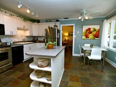 A chef's dream... large island for storage and Stainless Steel appliances.