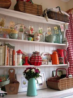 white hutch with old picnic baskets, blue and red items, red check curtains, seed packets used as bunting