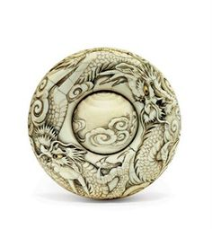 An Ivory Manju Netsuke   Signed Hakuho, Edo Period (19th century)   Boldly carved with two dragons, eyes inlaid in cowhorn, silvered cord attachment