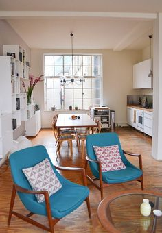 Nice teal chairs. Love the window and the warm feel.