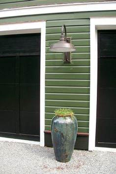 "estled in between the barn style garage doors is a large gooseneck barn light, otherwise known as our Hitchen Post Warehouse Shade. Measuring in with an 18"" shade diameter, it becomes ideal for those looking to illuminate large, outdoor areas or even for those needing commercial outdoor lighting."