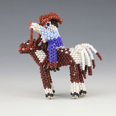 Zuni beadwork has evolved from tourist souvenirs to detailed pieces of folk art. First the Zuni artists carve a wooden form and then they bead over it, using the peyote stitch and seed or glass beads. With a continuous strand, Zuni beaders meticulously create wonderful patterns throughout their beadwork. This man riding a horse was hand beaded by Hollie Booqua. Unique Native American beadwork that will be a great addition to any collection. Artist Card, Native American Beadwork, Peyote Stitch, Nativity, Folk Art, Glass Beads, Contemporary Art, Arts And Crafts, Carving