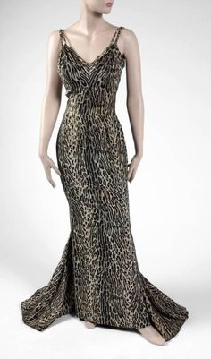 "A full-length silk jungle cat print gown worn by Jayne Mansfield on her 1957 European publicity tour. The bodice of this figure-hugging gown has double spaghetti straps, a padded bra, and is boned and intricately shaped to flatter the female curves. The long, straight skirt has a four-panel fishtail train with four layers of black netting. Both the skirt and train are weighted. ""Jayne Mansfield"" is written on the interior waistband. The straps have been repaired."