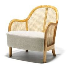 Arne Jacobsen: A rare, early easy chair with birch frame. Sides and back with woven cane. Seat upholstered with light fabric.1935