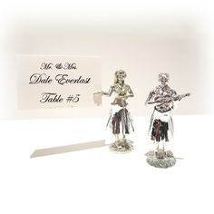 Hula Place Card Holders  Having a beach themed party? Our Hula Place Card Holders will be perfect. Each is made of high polished metal with a spring on the inside that makes them shake their metallic grass skirt. #hula #wedding #favors #beach #summer #hawaii
