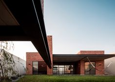 A brick volume containing a games room balances on steel beams that raise it above the sloping plot of this house in the Mexican city of Zapopan