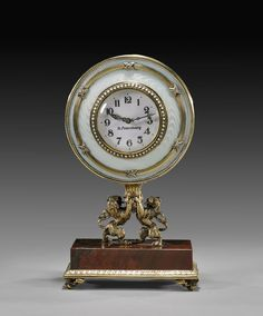 FABERGÉ-STYLE ENAMELED DESK CLOCK Russian Fabergé-style silver gilt and guilloche enamel desk clock; of circular form, the white porcelain f...