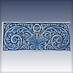 """Derby Pottery - DOUBLE SCROLL DIMENSIONS: 4.75"""" x 11"""" . Shown: Blue Gloss $55.00 per piece The Double Scroll design was originally a carved wood panel inset used in furniture building as an embellishment.  An image like this we call high Victorian. It is floral, very busy visually, and the composition carries the eye all over the place and back.  Ours is can be ordered in any of our 16 standard colors."""