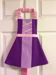 RAPUNZEL INSPIRED APRON  This adorable Disney inspired Rapunzel apron will definitely draw out a little girls imagination. Whether shes pretending to be a princess or trying to be mothers little helper, shes sure to have hours of fun dressing up. Easy on/off with elastic neck strap and back ribbon ties.  All fabrics are prewashed before the item is made to reduce shrinking. Care: Machine washable and line dry SIZING: There are three size options. Small 4/5 is sized for toddlers and ...
