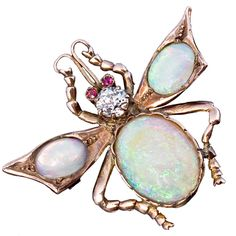 Victorian Jeweled Gold Insect Brooch Pin c.1890- probably English - circa 1890. An antique Victorian era 15K gold insect brooch (pin) with a diamond set head, ruby eyes, opal body and wings.
