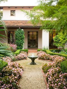 Step into a petal-packed courtyard! In this photo, a brick-edged gravel path is brightened with flowering begonias. A fountain at the center leads the eye into the garden and to the house. A crisp, boxwood hedge surrounds symmetrical gardens on each side of the walkway. Elegant, structural, and peaceful!