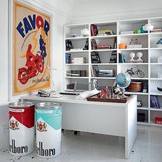 Grandes latas e um pôster coloridos alegram o escritório do arquiteto David Bastos no Rio de Janeiro. A base de todo o apartamento é branca