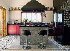 Aberta para a sala de jantar, a cozinha tem ilha de concreto queimado. O tapete de ladrilho hidráulico foi montado pela própria moradora com peças da Dalle Piagge (Foto: Edu Castello/Editora Globo)