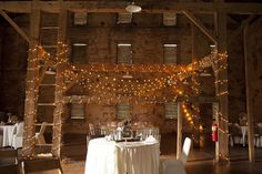 Simple sweetheart table stands beneath rustic barn beams covered in lights \\ www.johnparkerbands.com