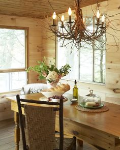 Unfinished tongue-in-groove pine walls give this cottage's dining area a natural look. A twig-wrapped chandelier is a playful nod to the outdoors.