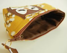 """This is a cotton canvas carry-all case featuring an all over yellow blossom print and a vinyl appliqued, Stewart the Owl""""!    The fabric is a medium weight cotton canvas featuring a japanese yellow blossom floral print. The inner body lining is brown duck canvas, and is thickened with stabilizer.    """"Stewart the Owl"""" is crafted from brown, white, and peanut brittle vinyl; and his pouch features mustard yellow rick-rack detailing.    The case features a tan zipper at the top with a tan vinyl…"""