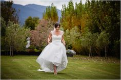 Bride walks across the lawn at wedding venue Marlborough Vintners Hotel