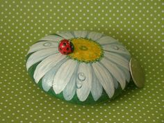 Hand painted flower rock. A rock painted into a white daisy with water droplets on the petals. A cute little lady bug has landed on it. The lady bird is also a rock! The rock measures about 3 (7.70cm) diameter and .75 (2.2cm) high The bug is glued on with stong glue. Its sealed with